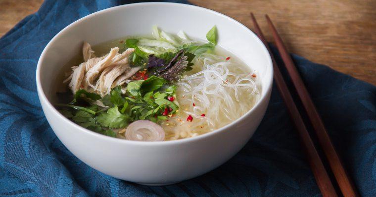 Kuřecí polévka s trhaným masem, rýžovými nudlemi, bylinkami a houbami Enoki